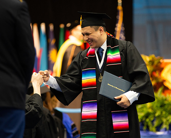 A student celebrates after receiving his diploma during a May commencement ceremony at UW-Stout.