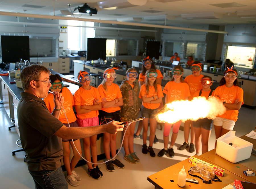 Matthew Ray, UW-Stout associate professor, demonstrates dust explosions and combustion of dust, to STEPS campers.