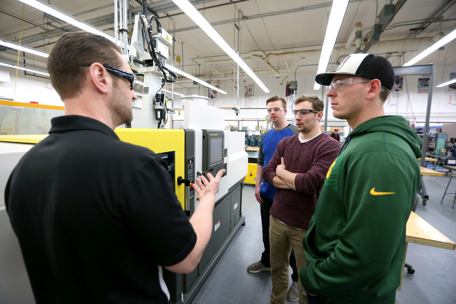 From left, Professor Adam Kramschuster talks with students Hunter Bartz, Bennett Conrardy and Jacob Halling next to a 55-ton Milacron Roboshot injecting molding machine.