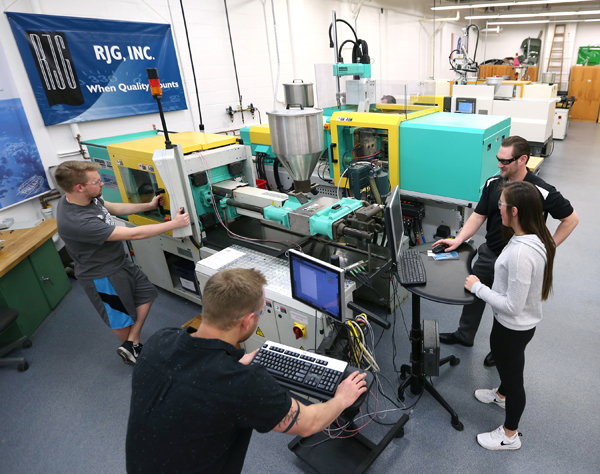 Students work with injecting molding machines in UW-Stout's plastics engineering lab.