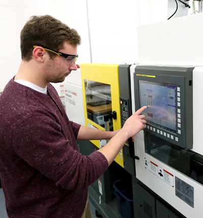 Plastics engineering major Bennett Conrardy programs a machine in the plastics engineering lab at UW-Stout.